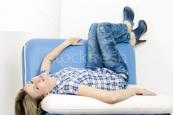 woman lying on sofa wearing jeans and denim clogs Stock photo © phbcz