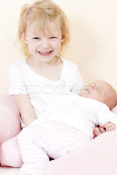 portrait of a little girl cradling her one month old baby sister Stock photo © phbcz