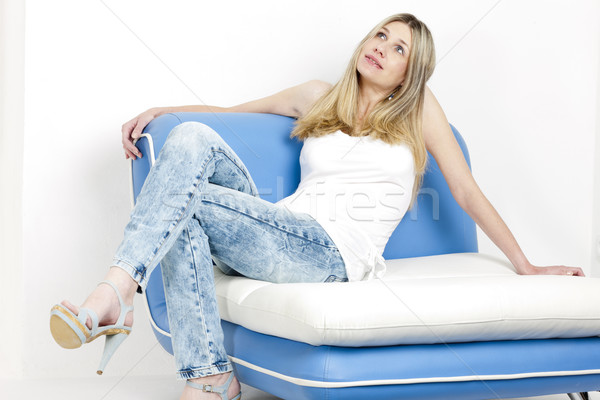 Donna seduta divano indossare jeans scarpe estive Foto d'archivio © phbcz