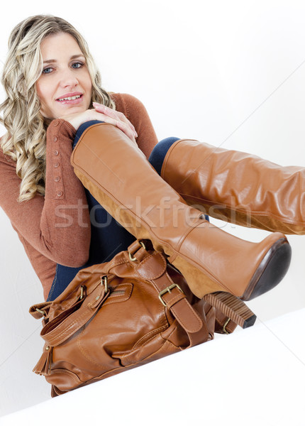 portrait of sitting woman wearing fashionable brown boots with a Stock photo © phbcz