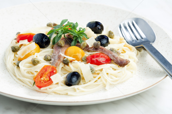 pasta with anchovies, capers and olives Stock photo © phbcz