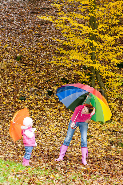 mother and her daughter with umbrellas in autumnal nature Stock photo © phbcz