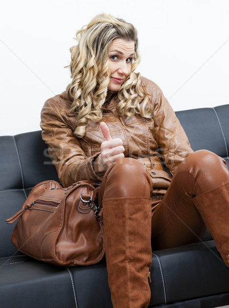 woman wearing brown clothes and boots with a handbag sitting on  Stock photo © phbcz