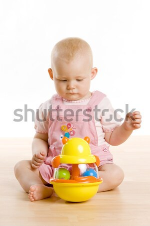 Stock photo: baby girl crawling towards a toy on the floor