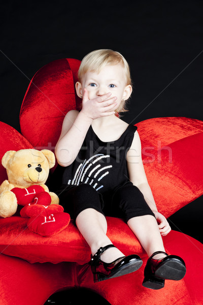 little girl with a teddy bear sitting on red armchair Stock photo © phbcz
