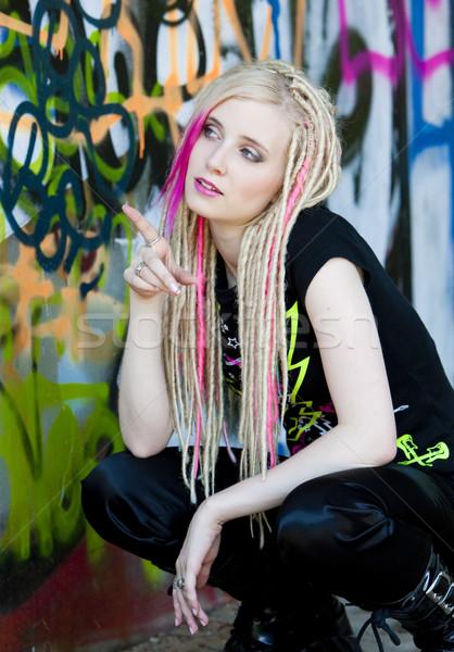 portrait of young woman sitting at graffitti wall Stock photo © phbcz