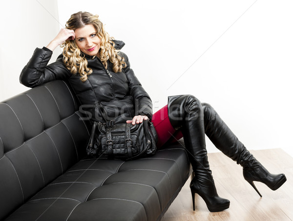 woman wearing fashionable clothes sitting with a handbag on a so Stock photo © phbcz