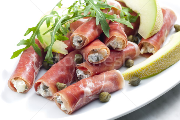 Parma ham rolls filled with cream cheese, Galia melon and capers Stock photo © phbcz