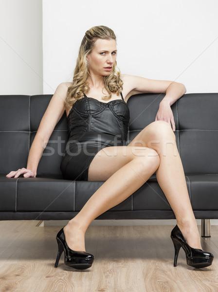 Nő visel fekete ruha ül kanapé cipők Stock fotó © phbcz