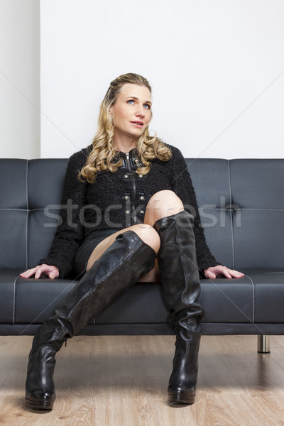 woman wearing black clothes and boots sitting on sofa Stock photo © phbcz
