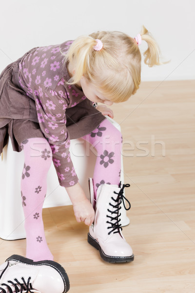 little girl putting on boots Stock photo © phbcz