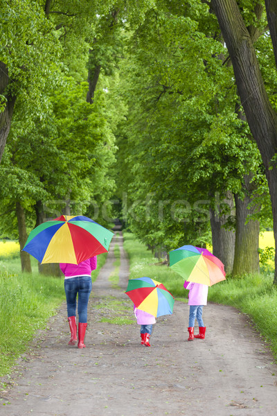 mother and her daughters with umbrellas in spring alley Stock photo © phbcz