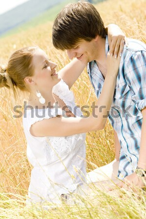 young couple sitting in grain field Stock photo © phbcz