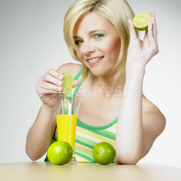 woman with a glass of juice and limes Stock photo © phbcz