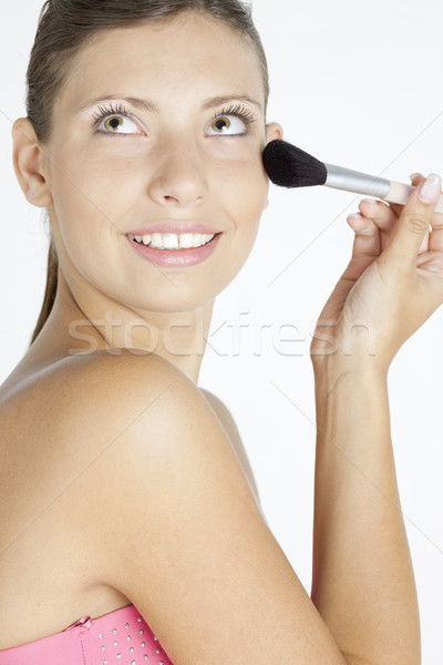 Stock photo: portrait of young woman putting on face powder