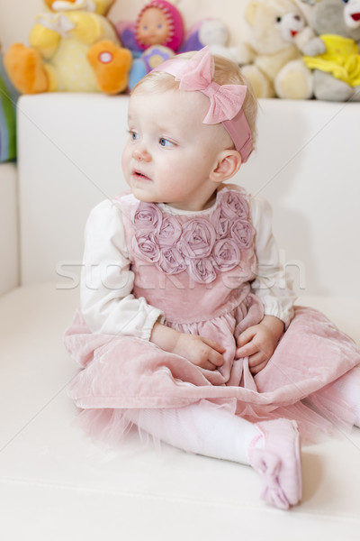 portrait of sitting toddler girl wearing pink dress Stock photo © phbcz