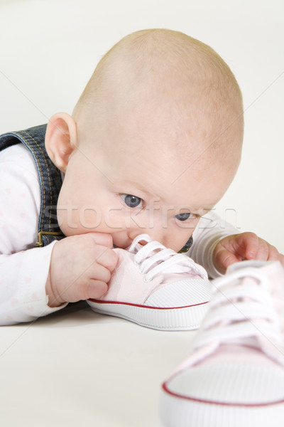 portrait of lying down baby girl holding shoes Stock photo © phbcz