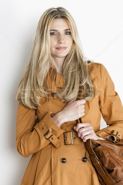 portrait of standing woman wearing brown coat with a handbag Stock photo © phbcz