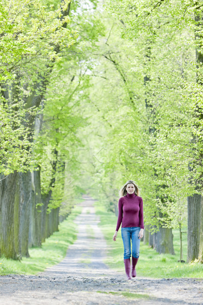 woman wearing rubber boots walking in spring alley Stock photo © phbcz