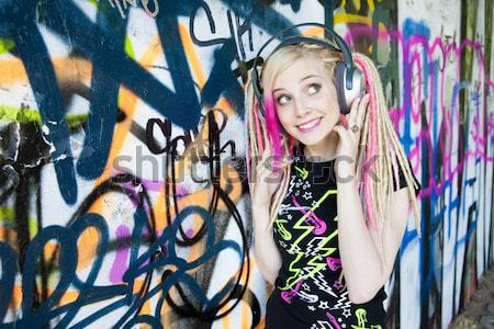 Stock photo: portrait of young woman standing at graffitti wall