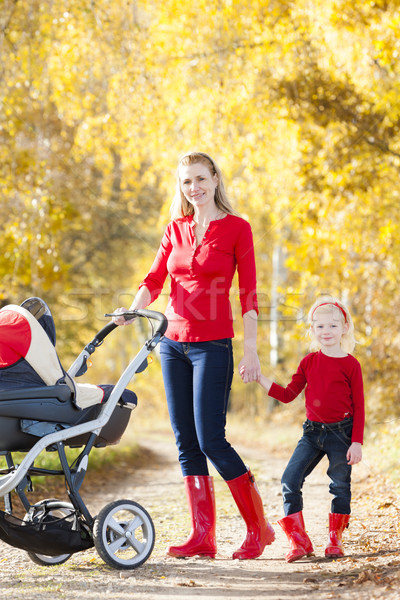 Stock photo: mother and her daughter with a pram on walk in autumnal alley