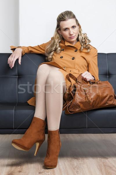 Kobieta brązowy płaszcz torebka posiedzenia Zdjęcia stock © phbcz