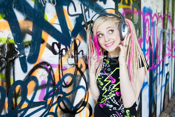 portrait of young woman with headphones at graffitti wall Stock photo © phbcz