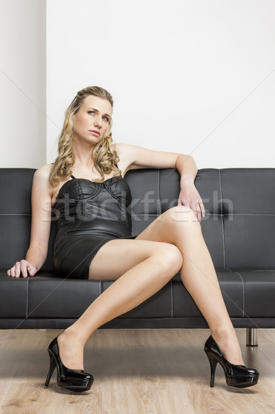 woman wearing black dress and pumps sitting on sofa Stock photo © phbcz