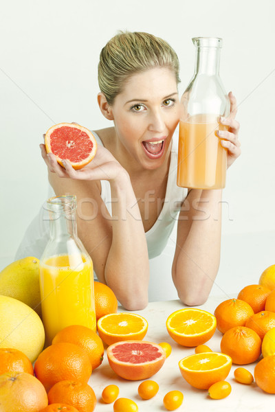 portrait of young woman with citrus fruit and orange juice Stock photo © phbcz