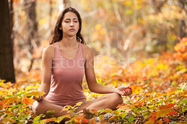 Stock photo: Young girl meditating in autumn park