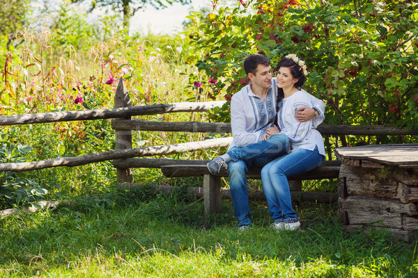 Lovely couple sitting on bench and flirting Stock photo © photobac
