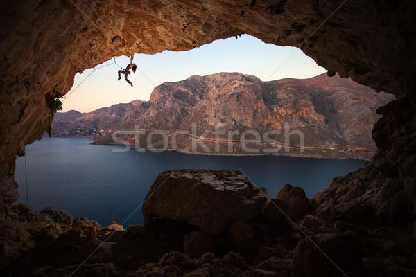 Stock photo: Silhouette of female rock climber on cliff in cave
