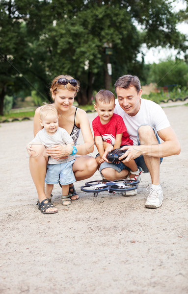 Young family with two boys playing with RC toy Stock photo © photobac