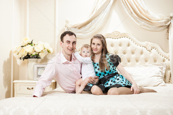 Stock photo: Young happy family with a baby on bed