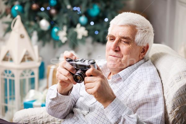 Idős férfi néz retró stílus kamera kirakat Stock fotó © photobac