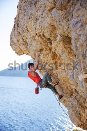 Female rock climber resting while hanging on rope Stock photo © photobac