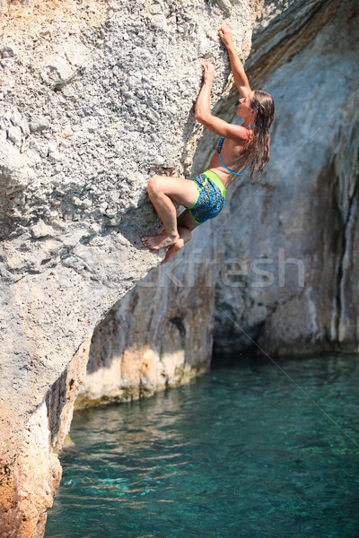 Deep water soloing, female rock climber on cliff Stock photo © photobac