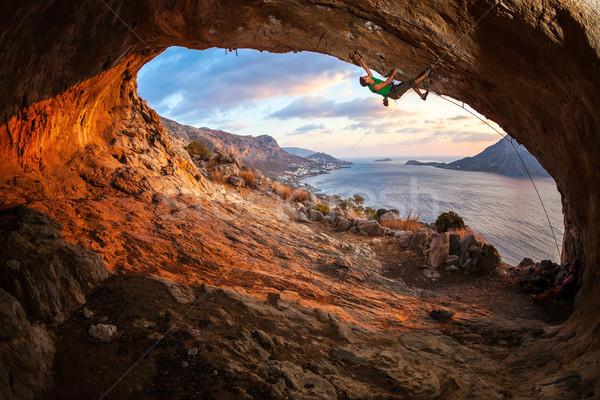 Maschio rock climbing tetto grotta tramonto Foto d'archivio © photobac