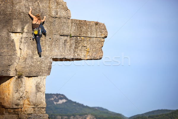 Young female free climber on a cliff Stock photo © photobac