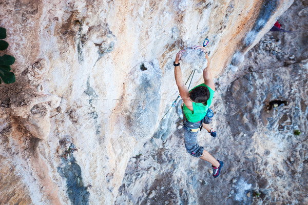 Climber holding on handhold while climbing cliff Stock photo © photobac