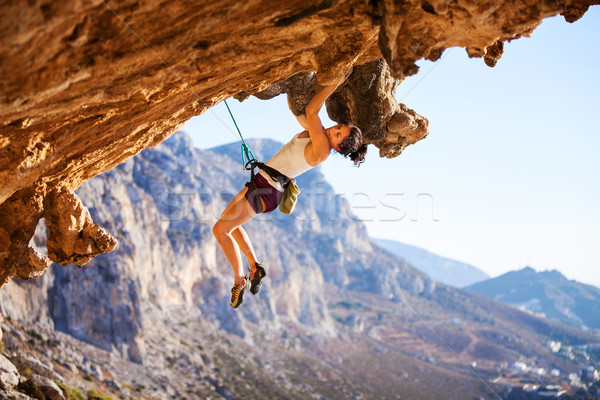 Stock photo: Young female rock climber on a cliff