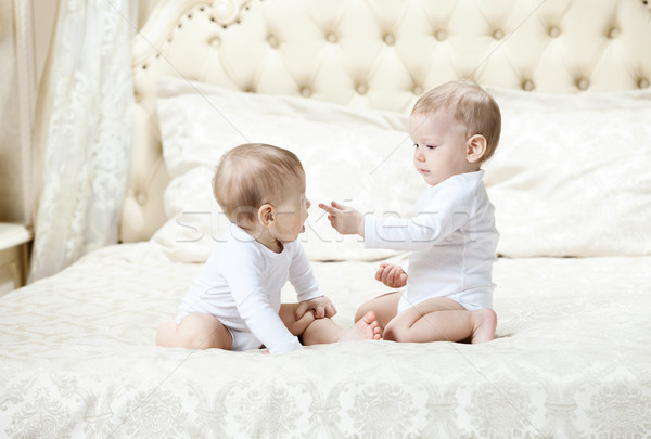 Two baby boys playing on bed Stock photo © photobac