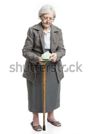 Senior woman counting money standing on white Stock photo © photobac