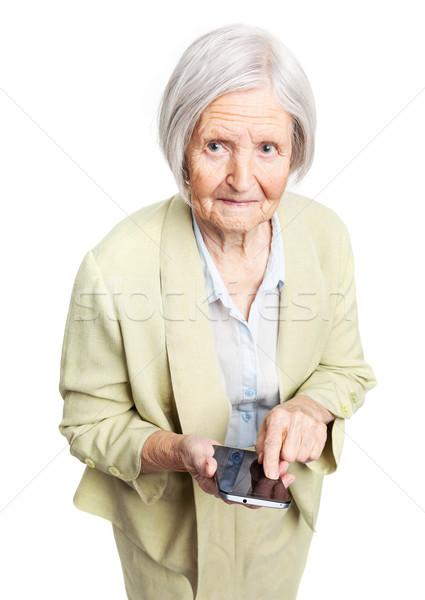 Senior woman holding mobile phone over white Stock photo © photobac