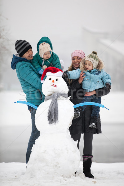 Young family with two sons beside snowman outdoors Stock photo © photobac