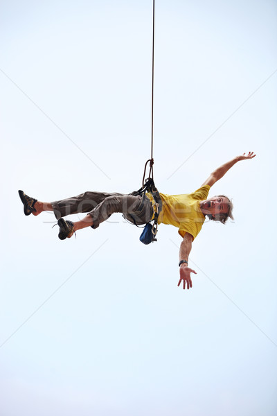 Happy rock climber hanging on rope Stock photo © photobac