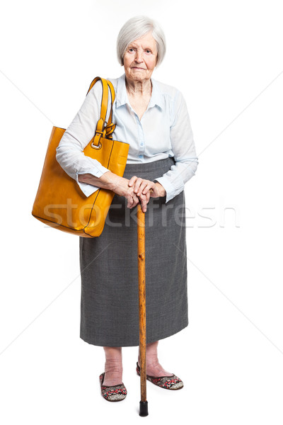 Elegant senior woman with walking stick on white Stock photo © photobac