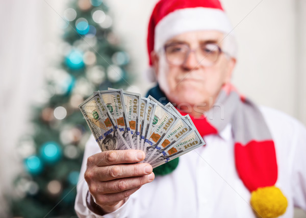 Man in Santa's hat holding money, hand in focus Stock photo © photobac