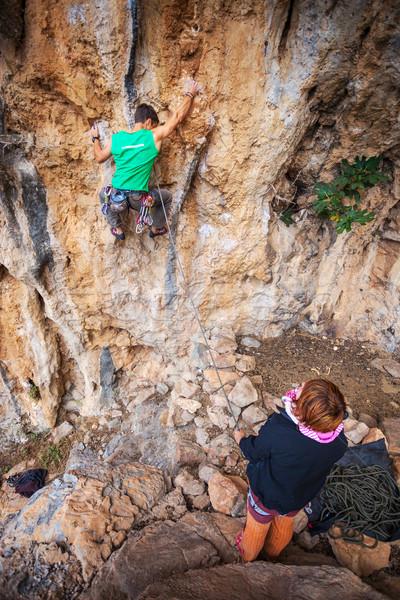 Man lead climbing on a cliff, belayer watching him Stock photo © photobac