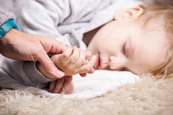 Mother holding son's hand while he is sleeping Stock photo © photobac